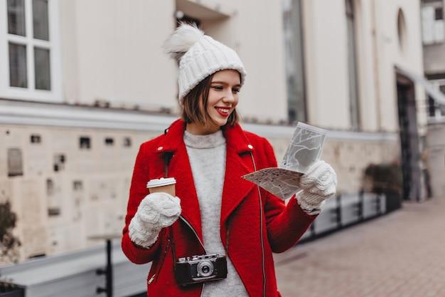 Piękny Turysta W Białym Kapeluszu I Czerwonym Płaszczu Trzymający Mapę, Zwiedzający Miasto. Portret Dziewczynki W Rękawiczkach Na Tle Budynku. Darmowe Zdjęcia
