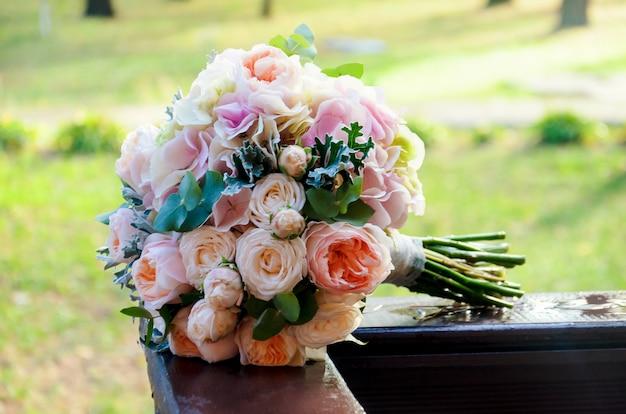 Piękny Uroczysty ślubny Bukiet Panny Młodej Z Róż I Eukaliptusa Leży Na Drewnianych Szynach Premium Zdjęcia