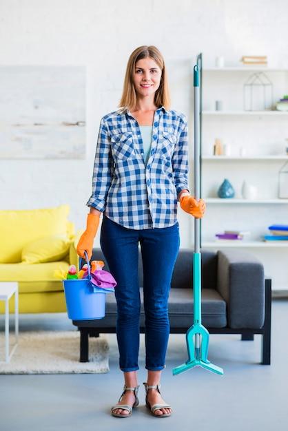 Piękny uśmiechnięty młodej kobiety mienia cleaning wyposażenie w rękach w domu Darmowe Zdjęcia