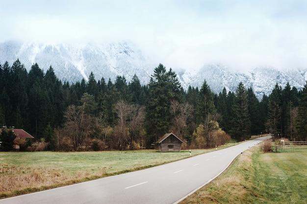 Piękny Uspokajający Droga Krajobraz Na Tle śnieżne Góry, Włochy, Dolomity. Krajobrazy Górskiej Drogi Późną Jesienią W Spokojnych, Ciepłych Kolorach. Podróż Samochodem Premium Zdjęcia