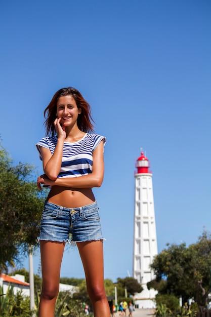 Piękny Widok Młoda Dziewczyna Z Krótkimi Cajgami I Błękitną Pasiastą Koszula Przeciw Latarni Morskiej. Premium Zdjęcia