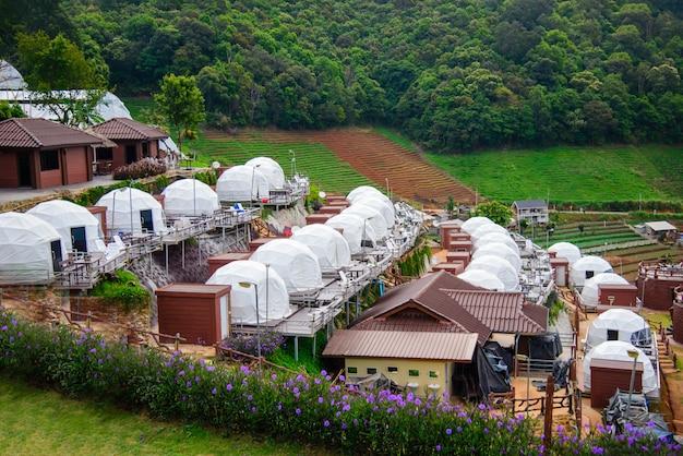 Piękny Widok Na Białe Namioty Kempingowe Z Górskim Krajobrazem Mon Jam I Kurortami O Wschodzie Słońca Rano. Premium Zdjęcia