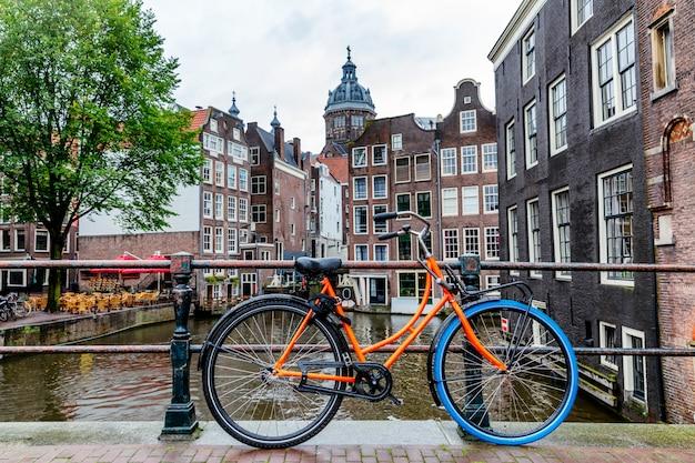Piękny widok na kanał w amsterdamie. domy na wodzie, rowery z kwiatami nm most. świetny pejzaż miejski. Premium Zdjęcia