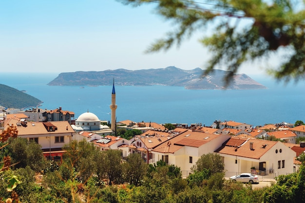 Piękny Widok Na Turkusowe Morze Z Meczetem I Tureckimi Domami Na Pierwszym Planie, Kurort Kas W Turcji. Pejzaż Morski W Turcji Premium Zdjęcia