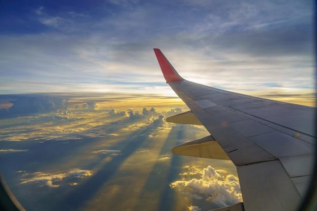 Piękny zachód słońca, niebo w widoku z góry, samolot latający widok z wnętrza samolotu okno podróży. Premium Zdjęcia
