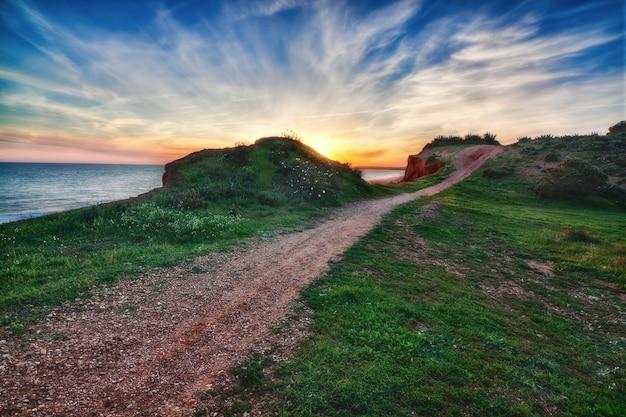 Piękny Zachód Słońca Z Widokiem Na Morze. W Pobliżu Drogi. Premium Zdjęcia