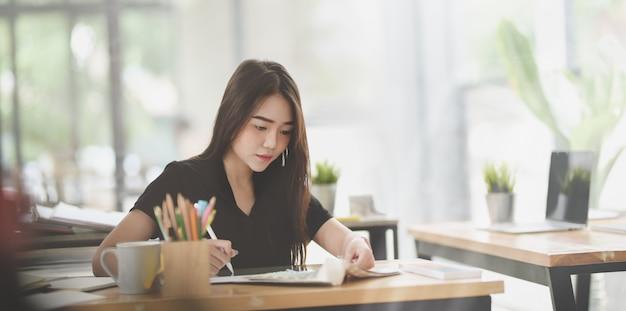 Piękny żeński freelancer pisze jej pomysle w notatniku Premium Zdjęcia