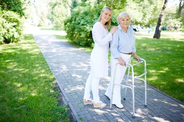 Pielęgniarka pomaga starszy kobieta używać balkonika Darmowe Zdjęcia
