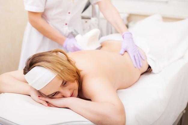 Pielęgnacja ciała. kobieta jest w trakcie zabiegu w klinice lipomassage Premium Zdjęcia