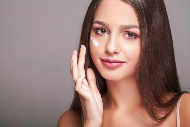 Pielęgnacja urody skóry. piękna kobieta szczęśliwa stosowania kremu kosmetycznego na czystą twarz. portret zbliżenie zdrowe uśmiechnięte modelki z naturalnym makijażem, świeżą miękką czystą skórę stosując balsam nawilżający Premium Zdjęcia