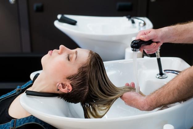 Pielęgnacja Włosów W Nowoczesnym Salonie Spa. Męski Fryzjer Myje Nastolatka Włosy Premium Zdjęcia