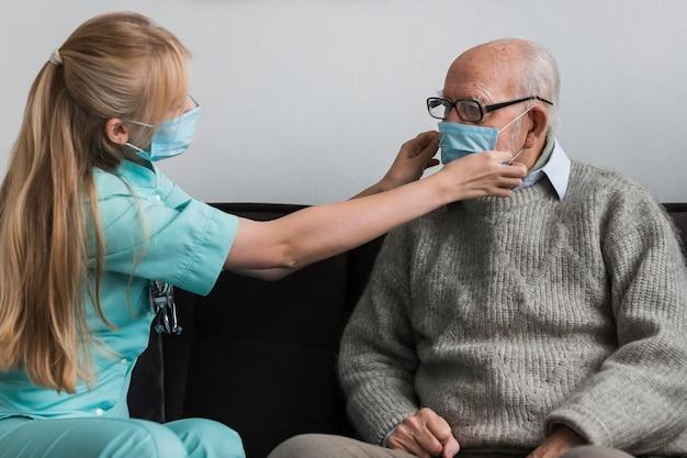 Pielęgniarka Dopasowująca Maskę Medyczną Starego Człowieka Darmowe Zdjęcia