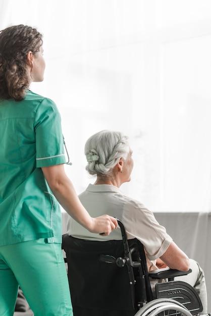 Pielęgniarka pcha niepełnosprawnego pacjenta na koła krześle w szpitalu Darmowe Zdjęcia