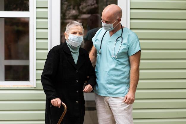Pielęgniarka Pozowanie Ze Starszą Kobietą Z Laską Darmowe Zdjęcia