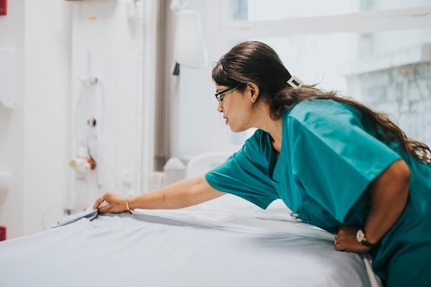Pielęgniarka robi łóżku w szpitalu Premium Zdjęcia