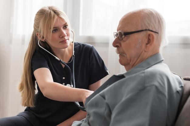 Pielęgniarka Sprawdza Bicie Serca Starego Człowieka Premium Zdjęcia