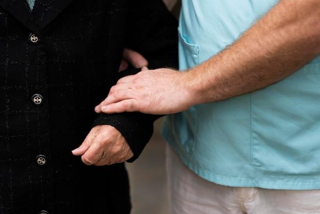 Pielęgniarka Trzymając Ramię Starszej Kobiety Premium Zdjęcia