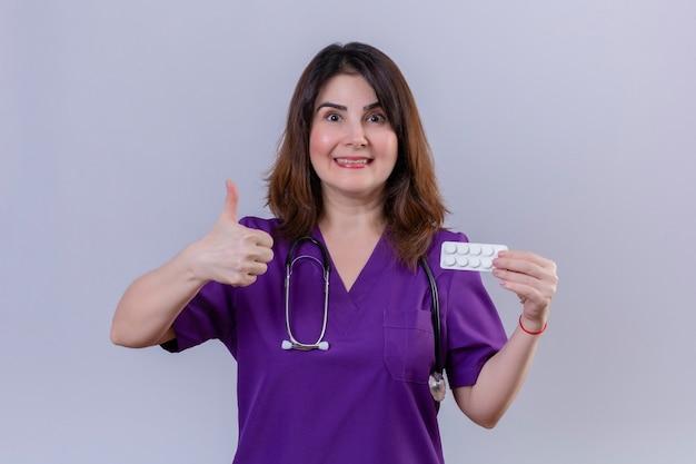 Pielęgniarka W średnim Wieku Ubrana W Mundur Medyczny I Ze Stetoskopem Trzymająca Blister Z Tabletkami Patrząc Na Kamerę Z Radosną Twarzą Pokazującą Kciuki Do Góry Stojącą Na Białym Tle Darmowe Zdjęcia