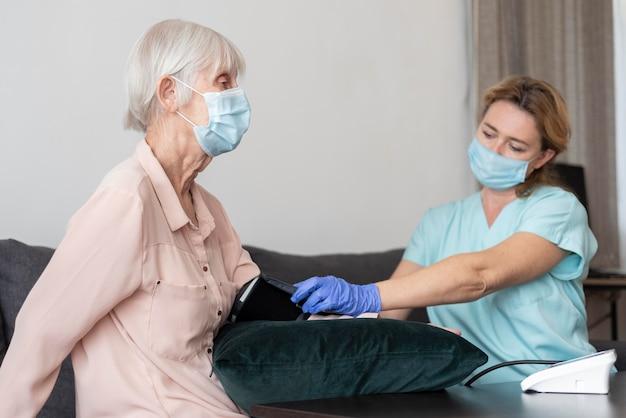 Pielęgniarka Za Pomocą Ciśnieniomierza Na Starszej Kobiecie Premium Zdjęcia