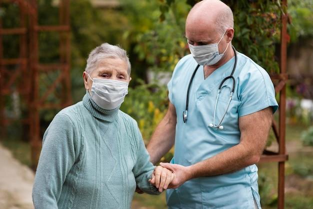 Pielęgniarki Mężczyzna Trzyma Rękę Starszej Kobiety, Aby Pomóc Jej Chodzić Darmowe Zdjęcia
