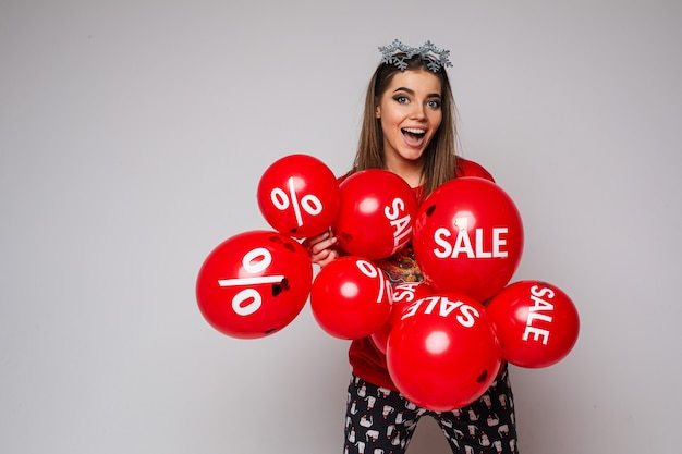 Pień Fotografia Podekscytowanej Brunetki Kobiety W Piżamie W Okularach Ozdobnych Płatka śniegu Na Głowie I Trzymającej Kilka Czerwonych Balonów Z Naklejkami Sprzedaży I Rabatów. Darmowe Zdjęcia