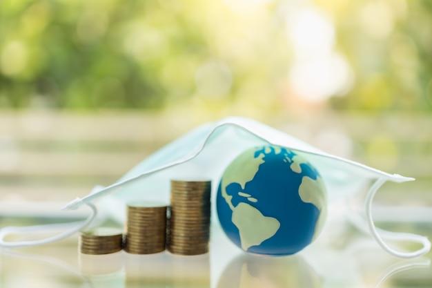 Pieniądze, Biznes, Opieka Zdrowotna Na Cornavirus (covid-19) Koncepcja Sytuacyjna. Mini World Ball Ze Stosem Złotych Monet Pod Maską Chirurgiczną Z Miejsca Na Kopię. Premium Zdjęcia
