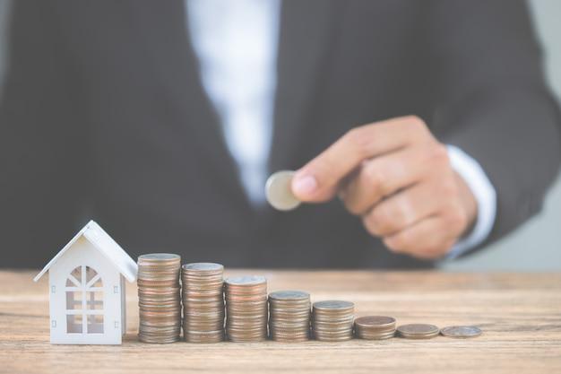 Pieniądze stosu monet przyspieszyć wzrost z modelu biały dom na drewnianym stole. Premium Zdjęcia