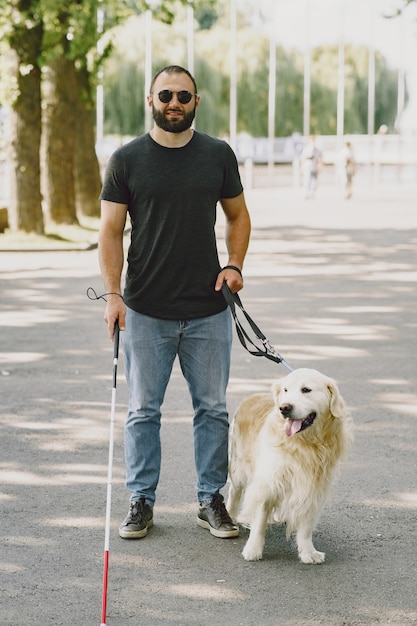 Pies Przewodnik Pomagający Niewidomemu W Mieście. Przystojny ślepy Facet Odpoczywa Z Golden Retriever W Mieście. Darmowe Zdjęcia