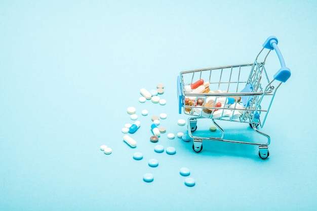 Pigułki I Wózek Na Zakupy Na Niebieskim Tle. Kreatywny Pomysł Na Koszt Opieki Zdrowotnej, Aptekę, Ubezpieczenie Zdrowotne I Koncepcję Biznesową Firmy Farmaceutycznej. Skopiuj Miejsce. Premium Zdjęcia