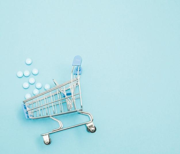 Pigułki I Wózek Na Zakupy Na Niebieskim Tle. Kreatywny Pomysł Na Koszt Opieki Zdrowotnej Premium Zdjęcia