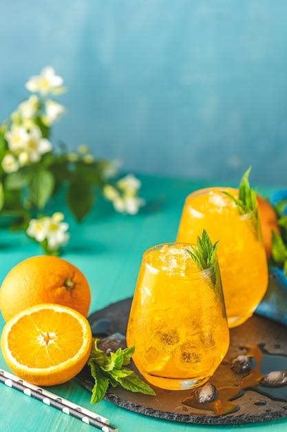 Pij Dwie Szklanki Pomarańczowego Lodu Ze świeżą Miętą Premium Zdjęcia