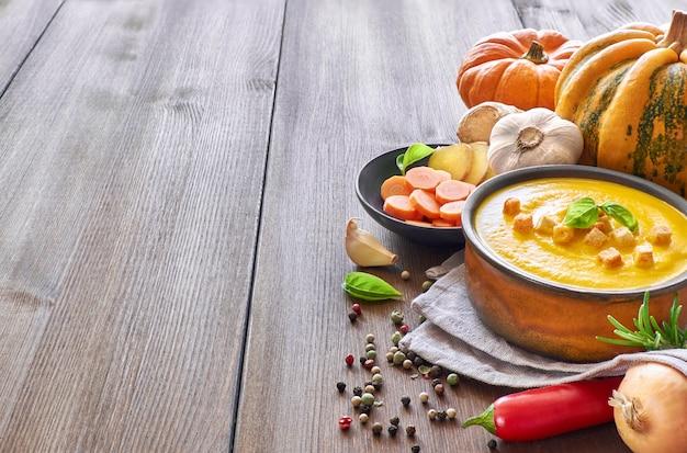 Pikantna zupa krem z dyni i marchwi z czosnkiem, cebulą. chili i imbir Premium Zdjęcia