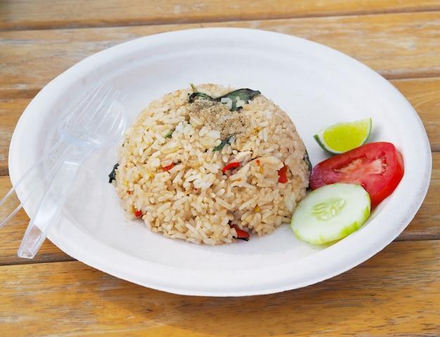 Pikantny ryż smażony na talerzu z recyklingu. tajski styl fast food. Premium Zdjęcia