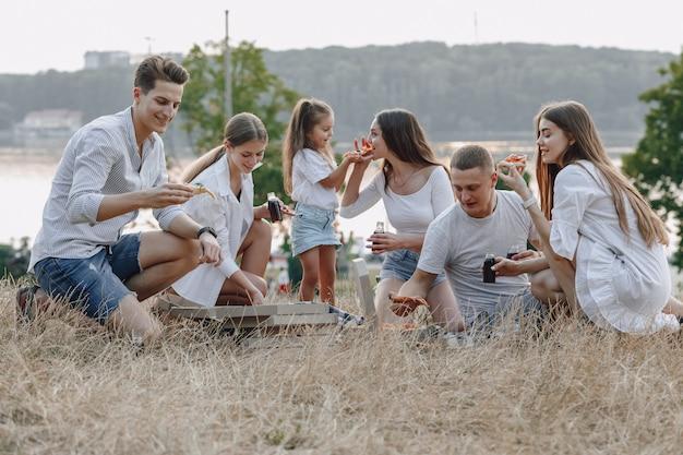 Piknikowi przyjaciele z pizzą i napojami, słoneczny dzień, zachód słońca, towarzystwo, zabawa, pary i mama z dzieckiem Premium Zdjęcia