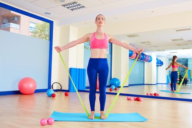 Pilates kobieta stojąca gumka ćwiczenia Premium Zdjęcia
