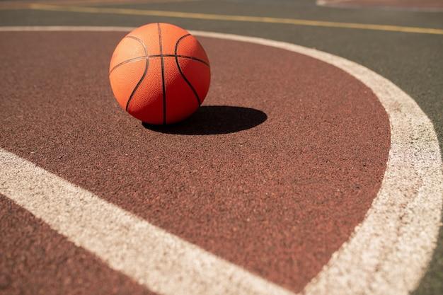 Piłka Do Gry W Koszykówkę Leżąca Na Boisku Lub Stadionie Pomiędzy Dwiema Białymi Liniami W Słoneczny Dzień Premium Zdjęcia