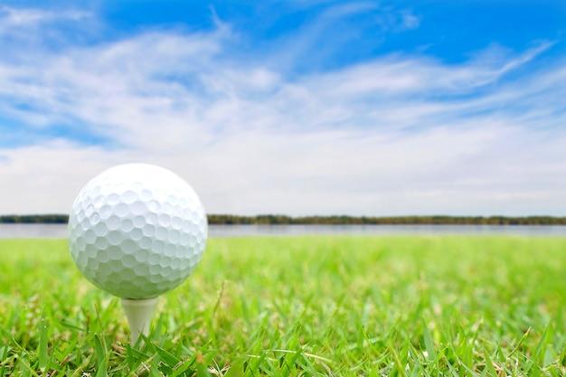 Piłka golfowa na trójniku w zielonej trawie. Premium Zdjęcia