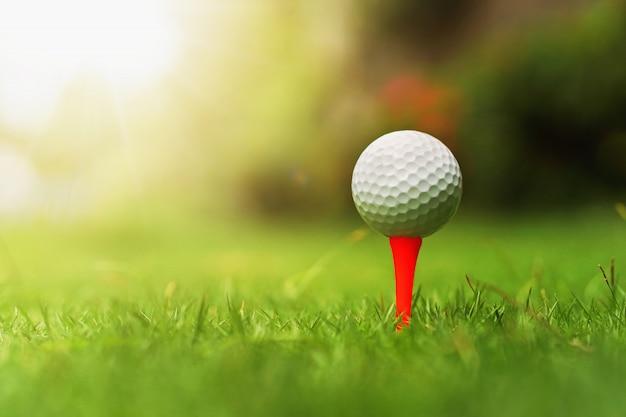 Piłka golfowa na zielonej trawie z wschodem słońca Premium Zdjęcia