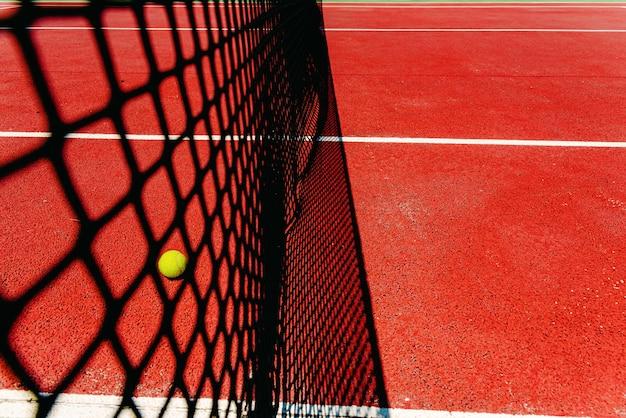 Piłka tenisowa na teksturowanej podłodze czerwonego boiska w pobliżu siatki po utracie punktu meczowego. Premium Zdjęcia