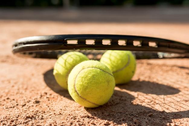 Piłki tenisowe i czarna rakieta Darmowe Zdjęcia