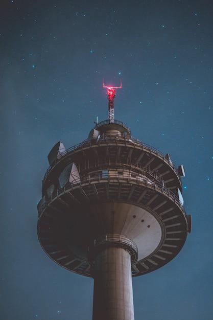 Pionowe Niski Kąt Strzału Szarej Wysokiej Wieży W Nocy Z Pięknymi Gwiazdami Darmowe Zdjęcia