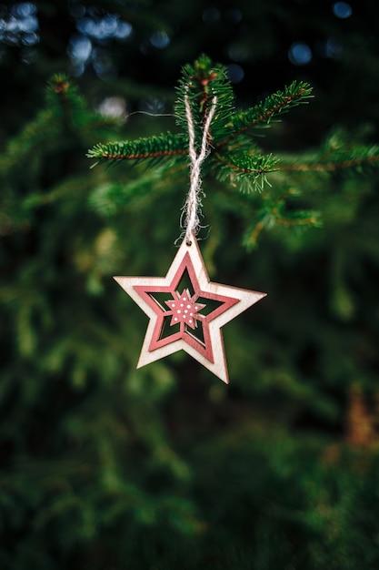 Pionowe Ujęcie Drewnianej świątecznej Ozdoby W Kształcie Gwiazdy Zwisającej Z Sosny Darmowe Zdjęcia