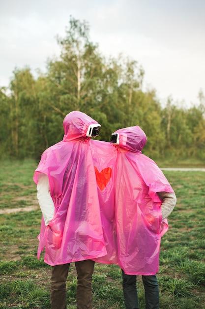 Pionowe Ujęcie Dwóch Osób Patrzących Na Siebie W Zestawach Vr W Różowym Plastikowym Płaszczu Przeciwdeszczowym Darmowe Zdjęcia
