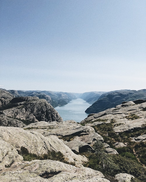 Pionowe Ujęcie Jeziora Otoczonego Przez Formacje Skalne Pod Bezchmurnym Niebem Darmowe Zdjęcia
