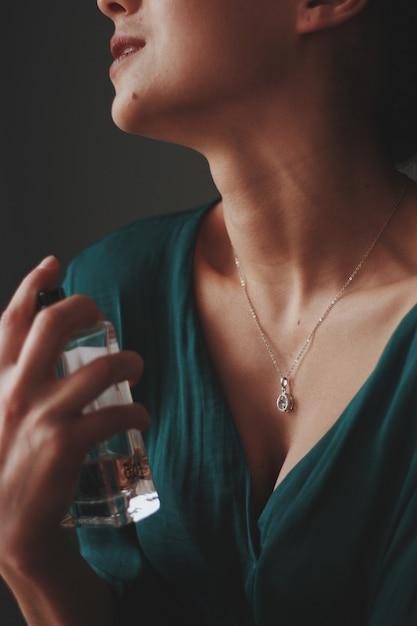 Pionowe Ujęcie Kobiety Noszącej Naszyjnik Z Diamentową Zawieszką Rozpylającą Na Nią Perfumy Darmowe Zdjęcia