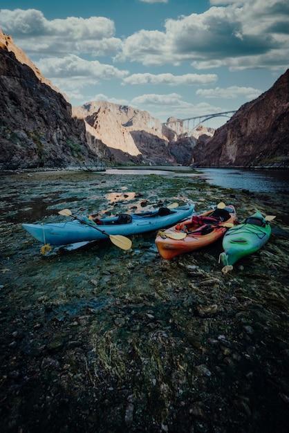 Pionowe Ujęcie Kolorowych łodzi Kajakowych Na Brzegu Jeziora W Górach Darmowe Zdjęcia