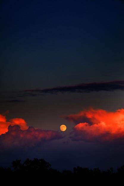 Pionowe Ujęcie Księżyca I Chmur Ognia Na Ciemnym Niebie Darmowe Zdjęcia
