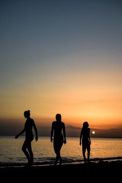 Pionowe Ujęcie Ludzi Idących Pod Zapierającym Dech W Piersiach Zachodem Słońca Nad Oceanem Darmowe Zdjęcia