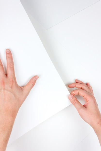 Pionowe Ujęcie Ludzkich Rąk Trzymających Kartkę Białego Papieru Darmowe Zdjęcia