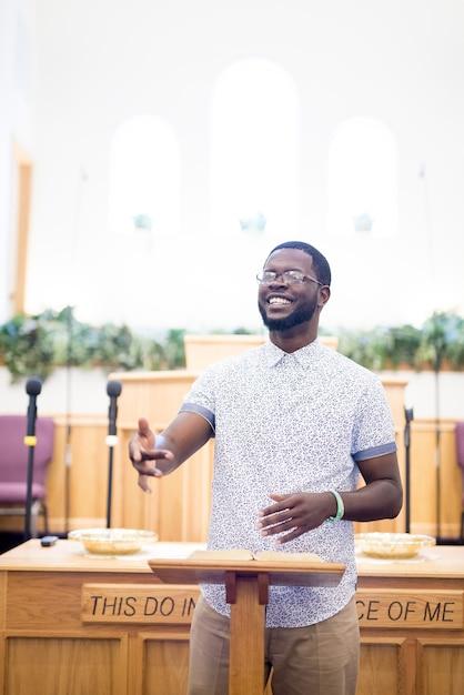 Pionowe Ujęcie Mężczyzny Czytającego Biblię W Pobliżu Stoiska W Kościele Darmowe Zdjęcia